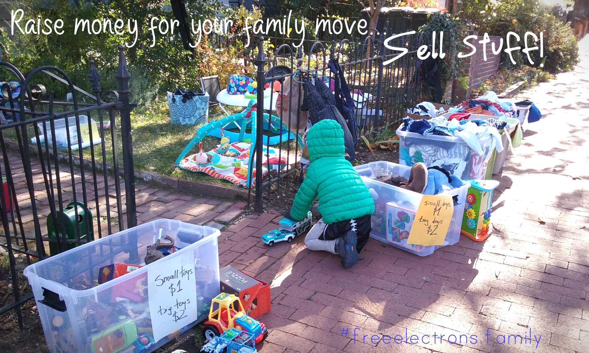 Picture of a yardsale with toys in plastic boxes and stuff on the lawn in a small yard and on the sidewalk.  A little kid, back turned, plays with a car toy.  Fundraising for a family move abroad.  Getting rid of all the things you think you need but don't even know you had.  Sell s*it!  It will set you FREE!