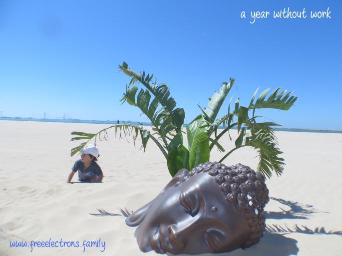 Picture of a boy with a baseball cap, a banana tree and the head of a Buddha on white smooth sands of a beach with Andalucian blue sky and the Cadiz bridge in the background.  Caption reads: a year without work by www.freeelectrons.family.  Description: Our family begins our year without work. . . from the winter chill of Washington DC to the warm embrace of Andalucia.