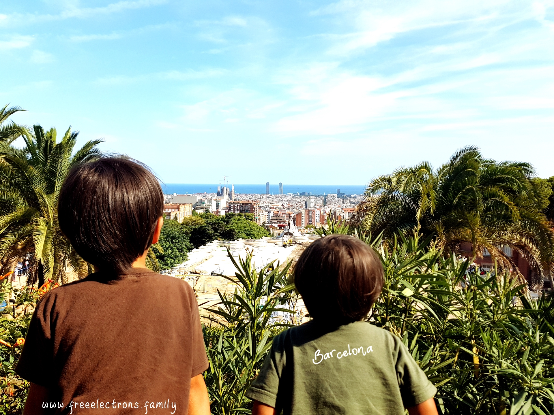 #FreeElectrons.Family - camping road trip Europe, Barcelona, Catalonia.   Two young kids enjoying the view of Barcelona from a viewpoint near the Gaudi House Museum.  Text reads: Barcelona and www.freeelectrons.com.