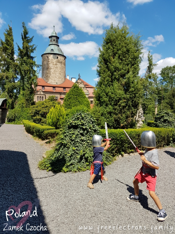 #FreeElectrons.Family - camping road trip Europe Poland, kids at play.  Two young boys in medieval soldier toy helmets and swords playing on castle grounds with lush gardens, under patch-cloudy blue skies.  Text reads: Zamek Czocha Poland (with 2 opaque interlocking hearts behind the text) and www.freeelectrons.com.