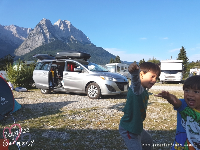 #FreeElectrons.Family - camping road trip Europe, Quechua and Mazda, Germany.  Kids having fun at a camping site with rocky mountain peaks in the background.  Behind them are RVs, a silver Mazda MPV 5 with a black Thule Roofbox, and part of a Quechua tent.  Postcard-like text reads: Zugspitze, Germany with an opaque image of two hearts behind the text and www.freeelectrons.com.