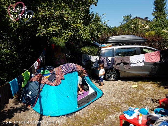 #FreeElectrons.Family - camping road trip Europe, Quechua tent, Austria.  A young boy at the entrance to a light blue Quechua tent talking to a younger boy standing outside.  They are in a small pitch lot surrounded by trees and bushes and flanked by a compact car with a black THULE roof box/luggage on top.  Clothes are drying on clothesline.  Text reads: Salzburg Austria (with 2 opaque interlocking hearts behind the text) and www.freeelectrons.com.