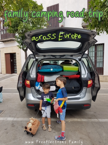 #FreeElectrons.Family - camping road trip Europe, Spain.  2 young kids in t-shirts and shorts await to get on a fully packed Mazda 5 to start their family fun summer camping road trip across Europe.
