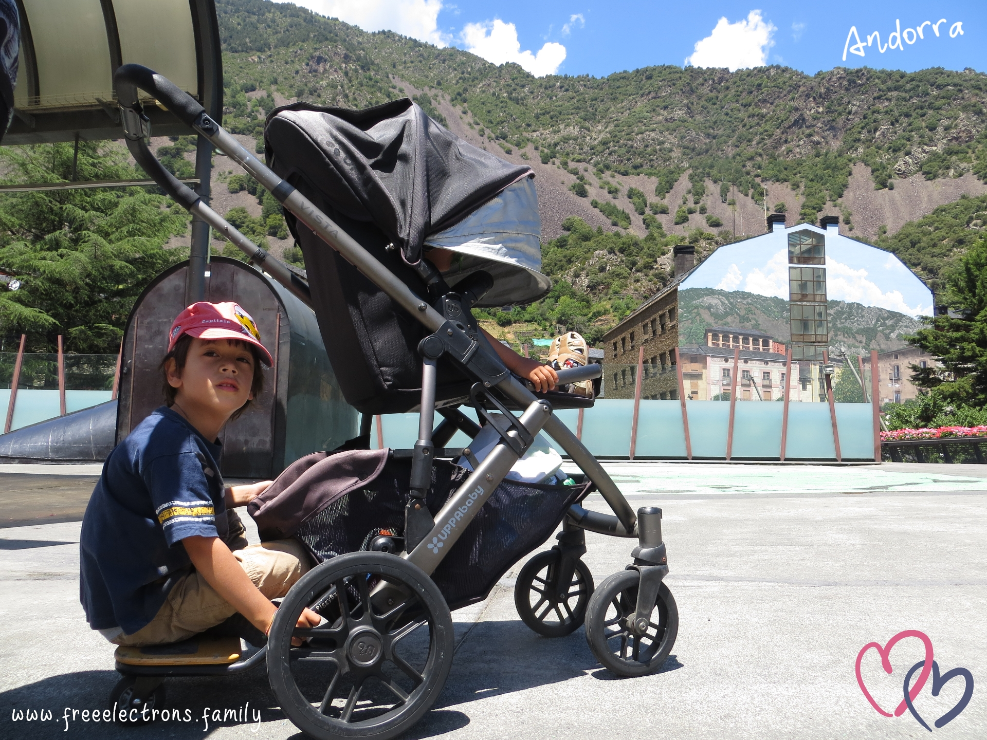 #FreeElectrons.Family - camping road trip Europe, UPPAbaby, kids chilling in Andorra.  Two young kids resting on an UPPAbaby VISTA stroller/pram at an empty plaza.  The older one  is sitting on the piggyback ride along board, looking past the camera.  The other one in the rumble seat.  A building with a landscape painting that blends in the background of green-patched mountain and, above, blue skies with white patches of clouds.  Text reads: Andorra; www.freeelectrons.com
