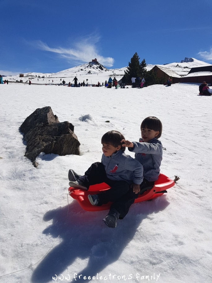 Two young boys on a red sled coming down a slope. One is pointing outward. The other one upfront looks directly and bravely ahead, holding onto to his older brother. In the background. blue sky over the peaks of the mountain atop Hoya de la Mora, in Sierra Nevada, province of Granada in Andalucia, Spain.