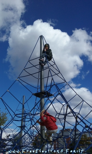 """Two young children at free play, climbing a tower connected with web-like ropes, at """"Ciudad de los Ninos""""  (City of Children).  Background Andalucian blue sky with some cumulus clouds."""