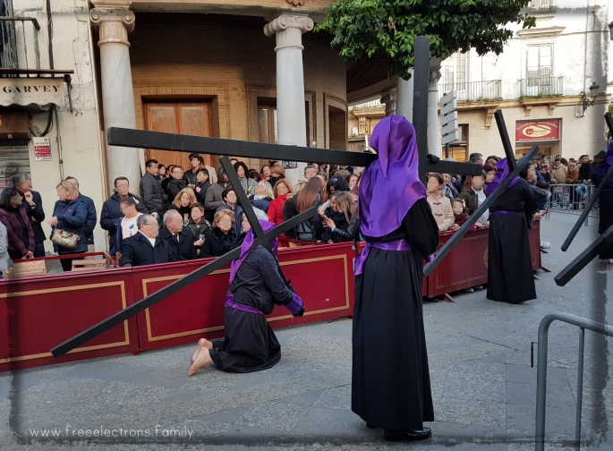 A cross-carrying procession during Holy Week (Semana Santa) along Calle Larga, Jerez de la Frontera, Spain.