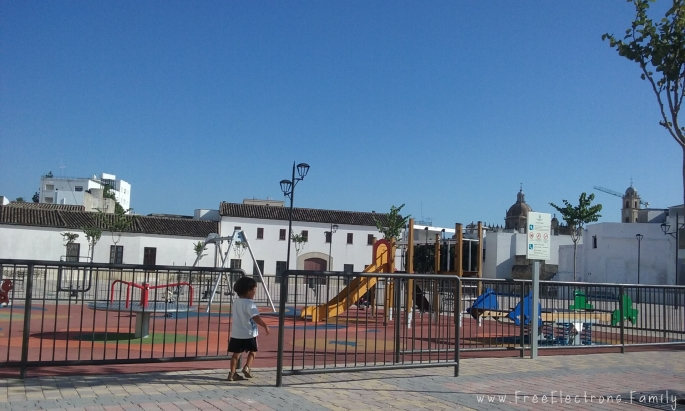 A single child plays in the middle of the day at a new-looking playground with the Cathedral de Jerez in the background.    Caption:  Hardly anyone comes out to this playground during siesta (around 2 to 5 pm).  Locals seemed to prefer early evening strolls and free play, which is understandable because the Andalucian sun is quite strong, even in the winter.