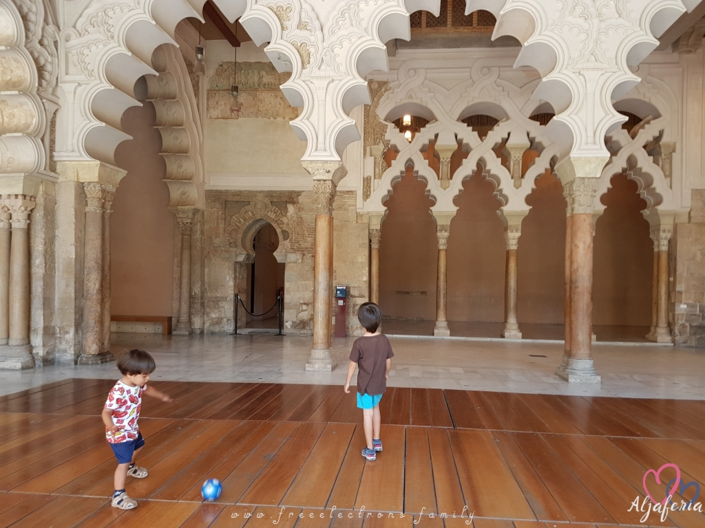 Two young children playing soccer in the the intricately decorated and beautifully renovated welcome hall of the Aljaferia. Text reads: www.freeelectrons.family and Aljaferia (with a drawing of 2 interlocking hearts behind it).