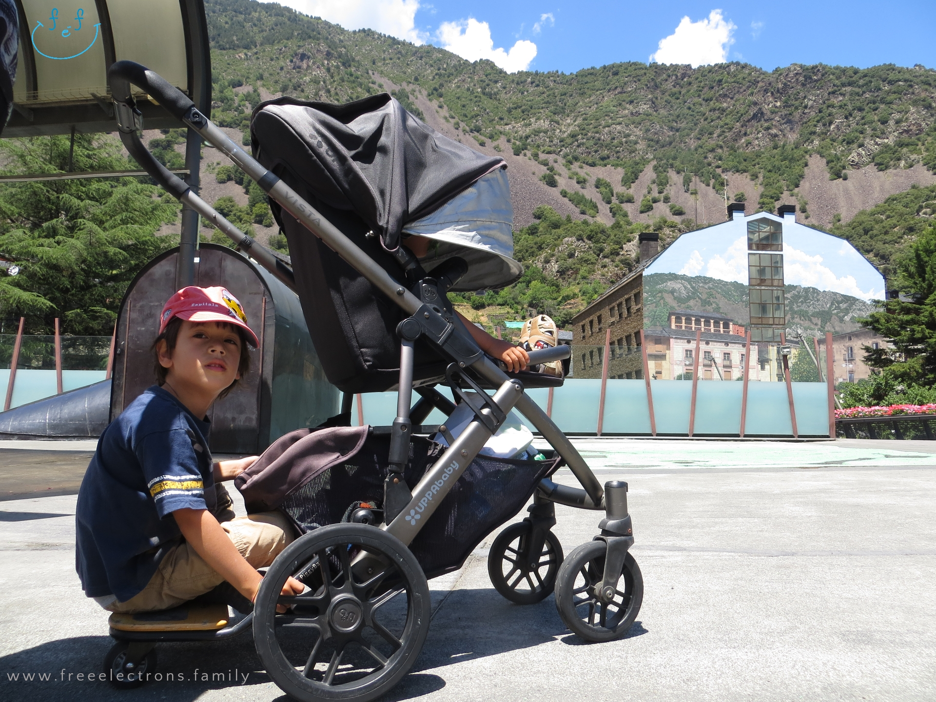 #FreeElectrons.Family - camping road trip Europe, Andorra by Uppababy stroller/pram.  Two young boys on a stroller in a wide open square, with a painted building that blends into a mountain background.  Text reads: www.freeelectrons.family