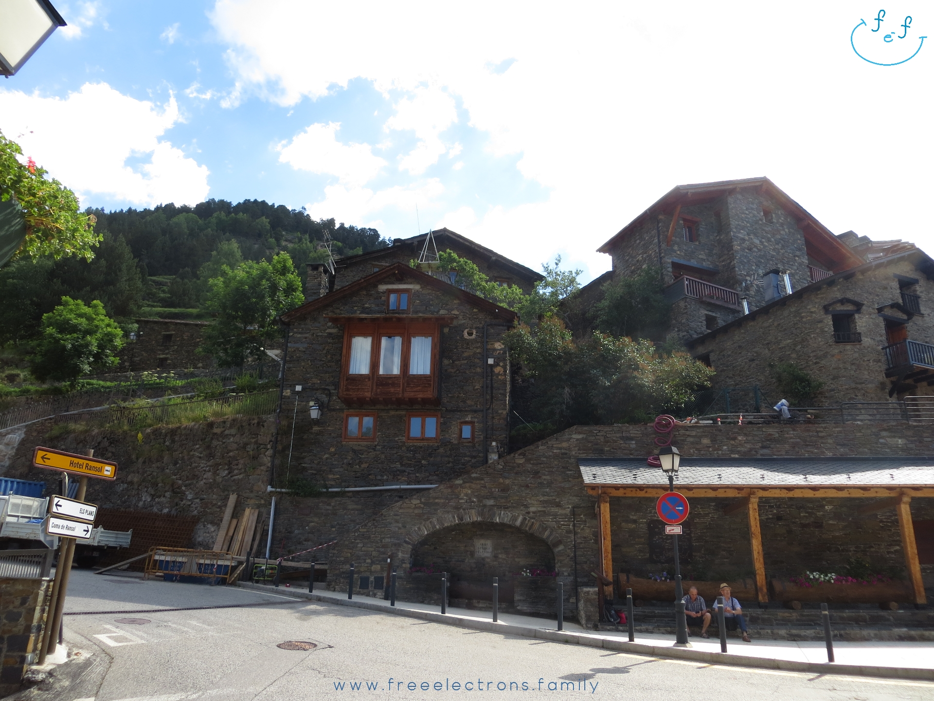 #FreeElectrons.Family - camping road trip Europe, Andorra Canillo.  Two elderly men sit on stone bench at a covered bus station; traditional Andorran stone houses in the background, under bright sky.