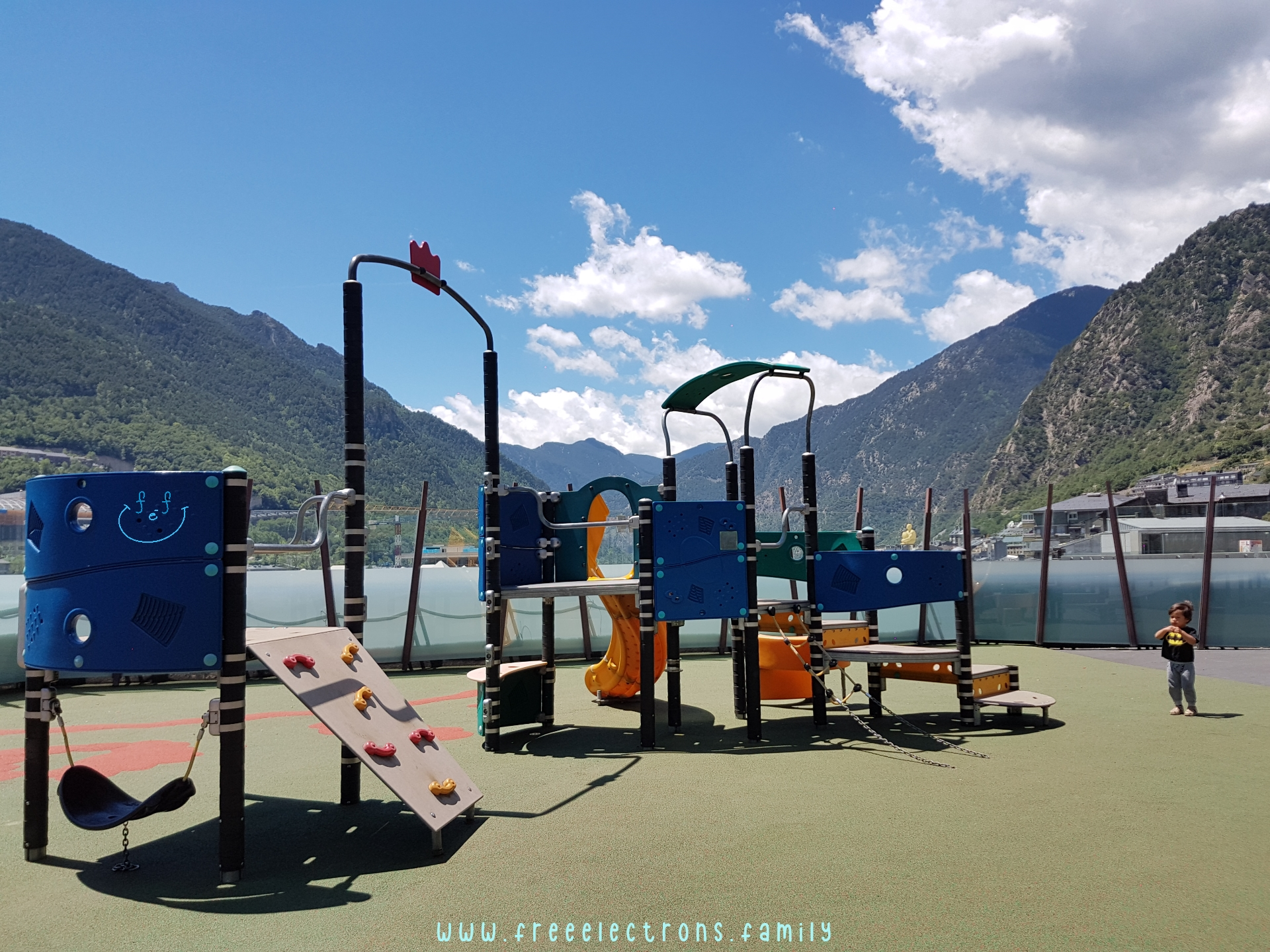 #FreeElectrons.Family - camping road trip Europe, Andorra centro playground.  A lone young boy in a modern playground with the mountains and blue bright sky in the background.  Text reads: www.freeelectrons.family