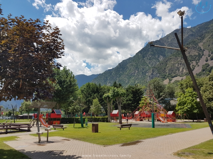 #FreeElectrons.Family - camping road trip Europe, Andorra playground.  A clean, modern and colorful playground in a park with lots of trees and mowed grass, with the mountainside and cloudy bright blue skies in the background.  Text reads: www.freeelectrons.family