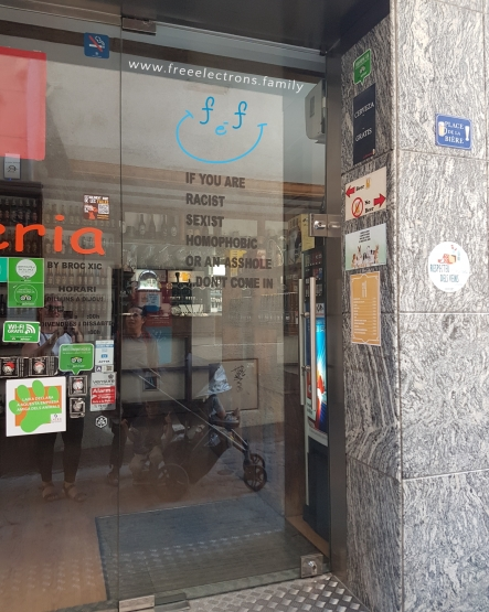 """#FreeElectrons.Family - camping road trip Europe, Andorran humour.  The glass-entrance of a store reads, """"If you are racist, sexist, homophobic or an asshole, DON'T COME IN"""".  www.freeelectrons.family"""