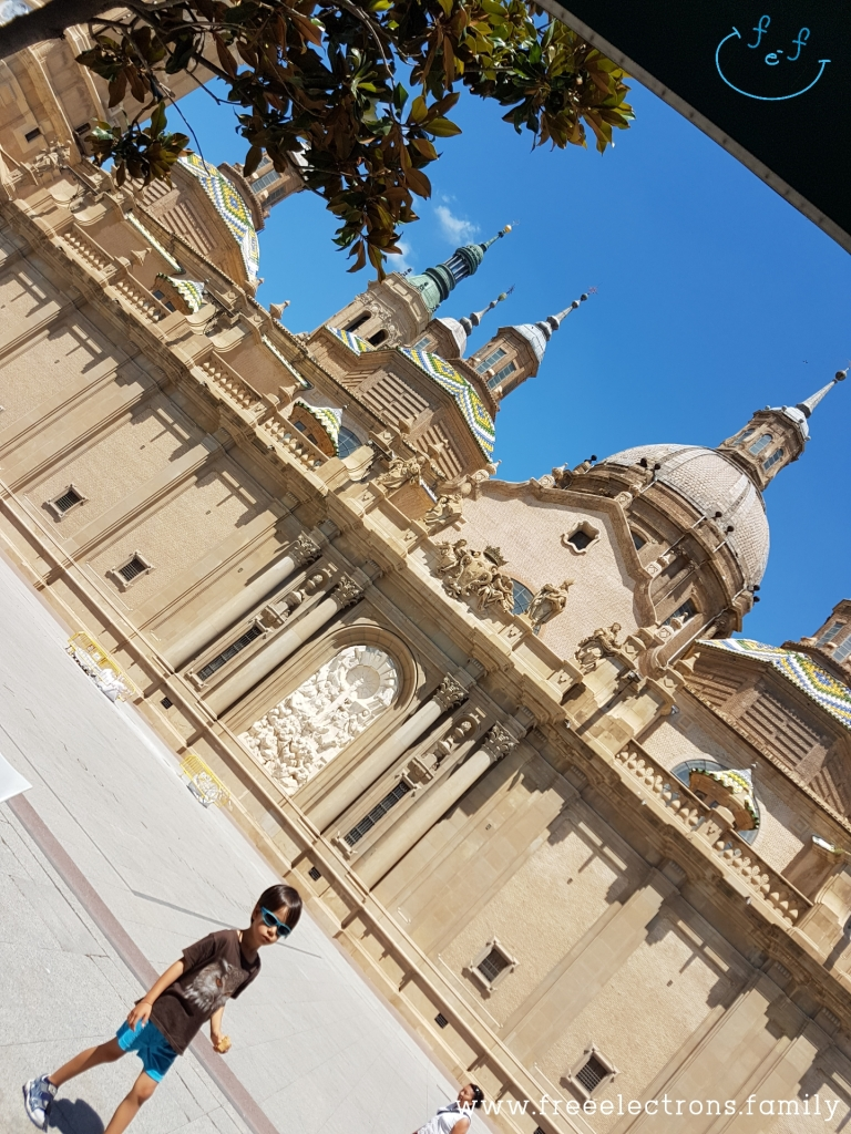 Third stop on our #FreeElectrons.Family summer camping road trip Europe, Day 5 in Zaragoza.   A young child  walks on the wide-open plaza/square in front of the Cathedral-Basilica of Our Lady of the Pillar.