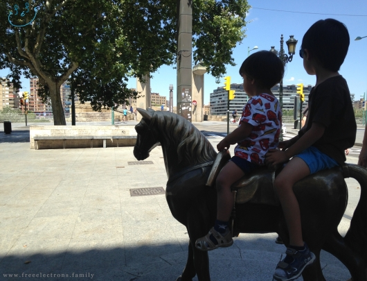 Two young boys on horseback (monument of one horse) entering the city from the Puente de Piedra (Stone Bridge) over the Ebro river.   Third stop on our #FreeElectrons.Family summer camping road trip Europe, Day 5 in Zaragoza.