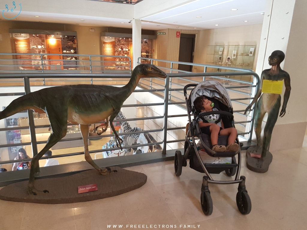 A child sleeps in a stroller/pram, fitting right in between an I-love-to-eat-little-kids-asaurus and a I-just-got-out-of-Roswell alien... at the National Museum of Natural History. #FreeElectrons.Family - camping road trip Europe, Madrid Science Museum alien dinosaur.