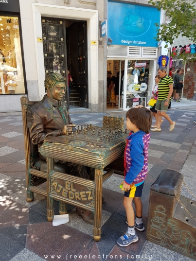 """A young boy enjoying a game of """"El Ajedrez"""" ... or chesss in a street of Madrid."""