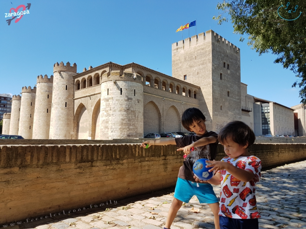 "Two young boys at free play at the tree-lined park just outside the Aljaferia. The EU, Spanish and Aragon flags fly above the castle-fortress in the background. Text reads: Zaragoza with a symbol of a heart and an arrow behind it, and ""www.freeelectrons.family""."