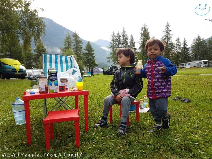 Two young kids having breakfast outdoors, at a camping site, with the Swiss alps in the background.  Nie ma jak śniadanko na świeżym powietrzu z widokiem na szwajcarskie Alpy! Nawet mi sok owocowy smakuje tutaj! Kemping Zernez, Szwajcaria.  There's nothing better than having breakfast al fresco with the view of the Swiss Alps.  Even my vegetable juice tastes good here!  www.freeelectrons.family