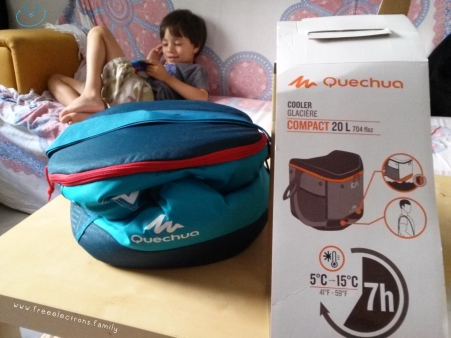 collapsed Quechua 20L compact cooler and box with a young boy smiling and sitting on a couch in the background.  Text reads: www.freeelectrons.family.  #FreeElectrons.Family - camping Europe, what to bring