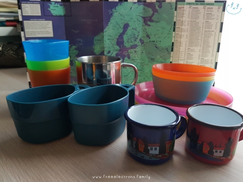Camping eating utensils (cups, plates, etc.).  Text reads: www.freeelectrons.family.  #FreeElectrons.Family - camping Europe, what to bring