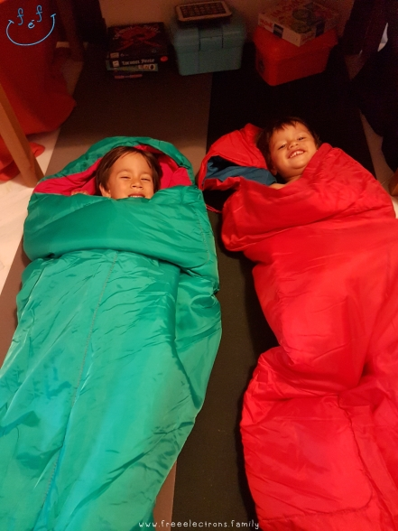 Two young boys testing their sleeping bags at home, wearing big smiles.  Text reads: www.freeelectrons.family.  #FreeElectrons.Family - camping Europe, what to bring