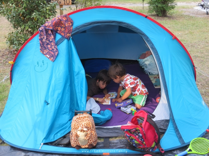 Two young boys inside a camping tent, reading.  Text Reads: www.freeelectrons.family.  #FreeElectrons.Family - camping Europe, what to bring, tent.