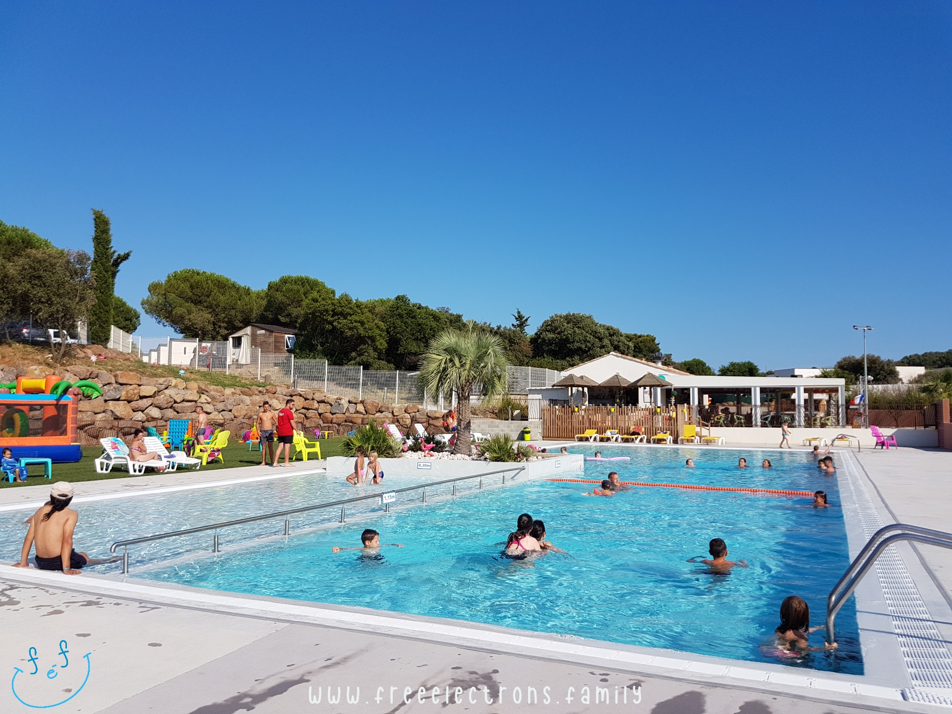 A not-so-full-of-people swimming pool divided in 3 areas, including a kiddie pool, under a summer clear blue sky.  #FreeElectrons.Family - camping road trip Europe, Agde France.