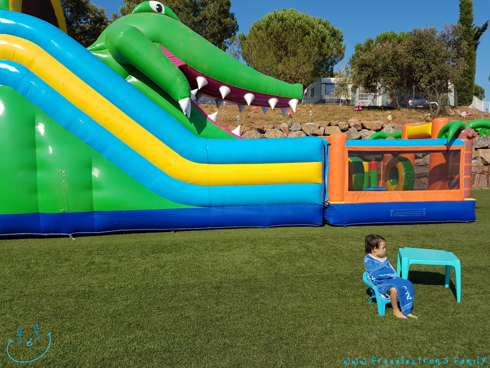 A young boy wrapped in a towel, sitting on a kids chair on green grass, next to a huge crocodile-themed, jump-and-slide,  inflatable play structure.  #FreeElectrons.Family - camping road trip Europe, Agde France.