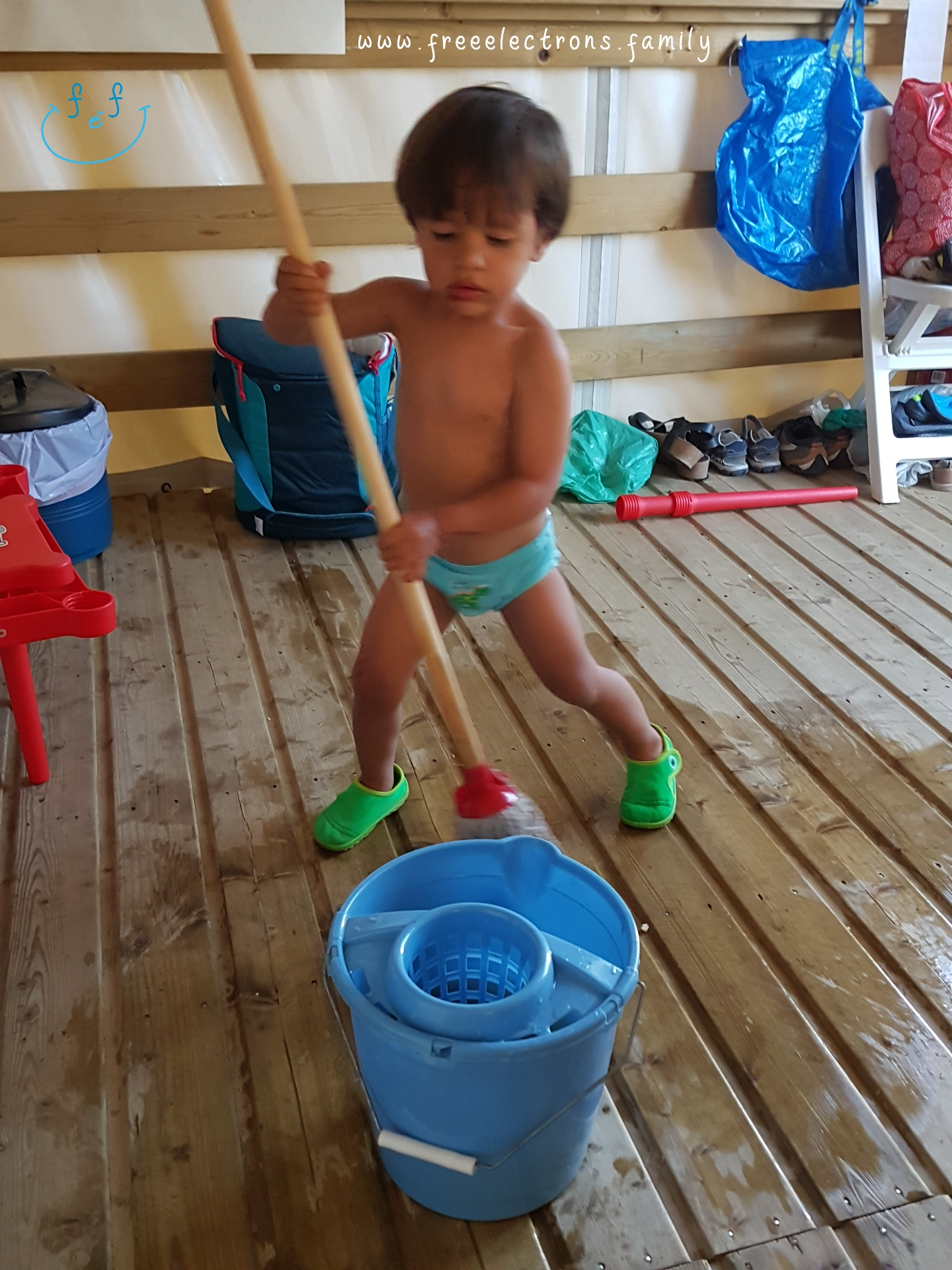 A young boy, shirtless, cleans up with a broom in a camping cabin.  #FreeElectrons.Family - camping road trip Europe, Agde France.
