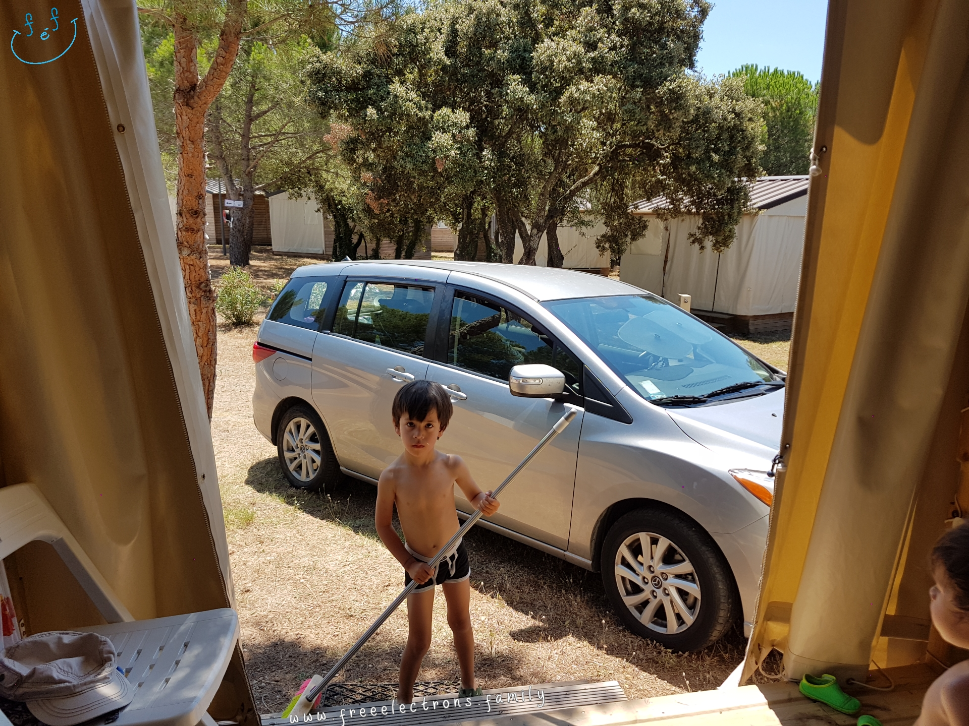 A young boy, shirtless, cleaning up with a broom in front of  camping cabin.  A younger boy looks at him from a patio.  #FreeElectrons.Family - camping road trip Europe, Agde France.