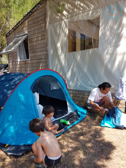 A father with 2 young kids setting up tent a tent next to a cabin.  #FreeElectrons.Family - camping road trip Europe, Agde, France.