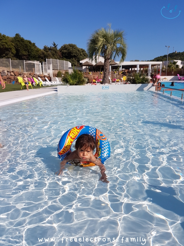 "A toddler swims in a kiddie pool with a ""salvabida"" (lifesaver).  #FreeElectrons.Family - camping road trip Europe, Agde France."
