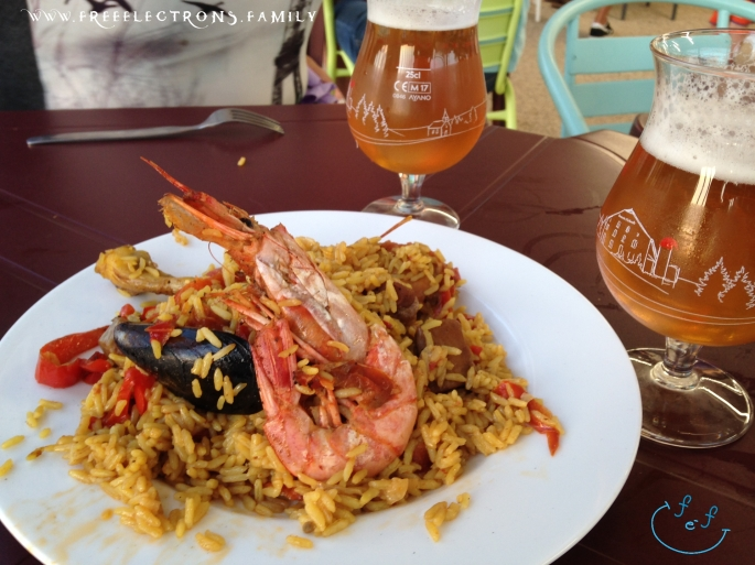 A paella (rice) dish with shrimp, mussel, chicken, strip of red bell pepper, with two sexy glasses of amber-colored local beer.  #FreeElectrons.Family - camping road trip Europe, Agde France.