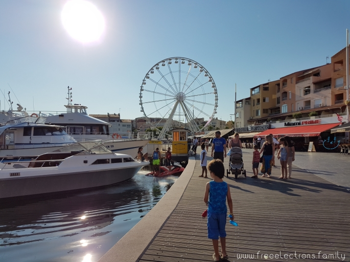 A young boy walks on a boardwalk of a marina, with others in the background, ahead of him.  There are modern boats on the water and a grand ferris wheel up ahead.  #FreeElectrons.Family - camping road trip Europe, Cap d'Agde France.