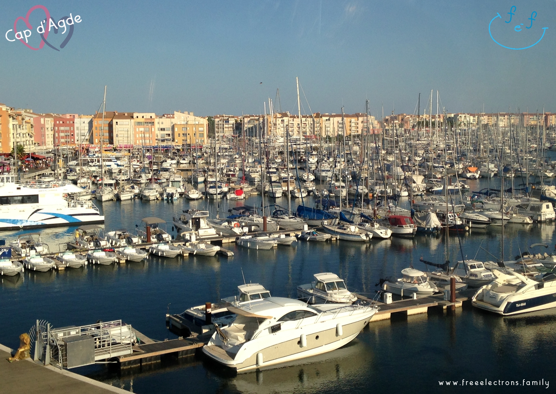 A view (from the ferris wheel) of Cap d'Agde's marina packed with modern boats in the foreground and buildings in the background.  #FreeElectrons.Family - camping road trip Europe, Cap d'Agde France.