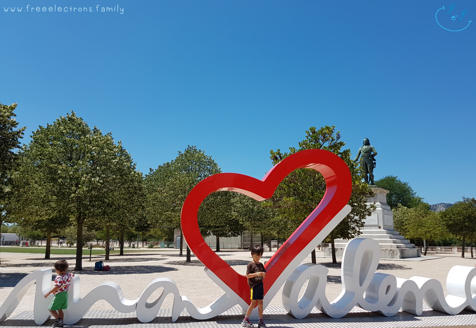 "Two young boys at the ""heart"" of Valence with a monument and trees in the background.   #FreeElectrons.Family - camping road trip Europe, Valence."
