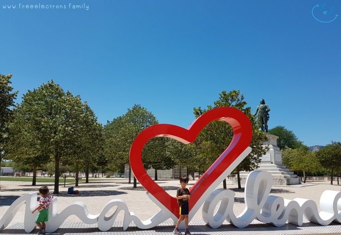 """Two young boys at the """"heart"""" of Valence with a monument and trees in the background.   #FreeElectrons.Family - camping road trip Europe, Valence."""