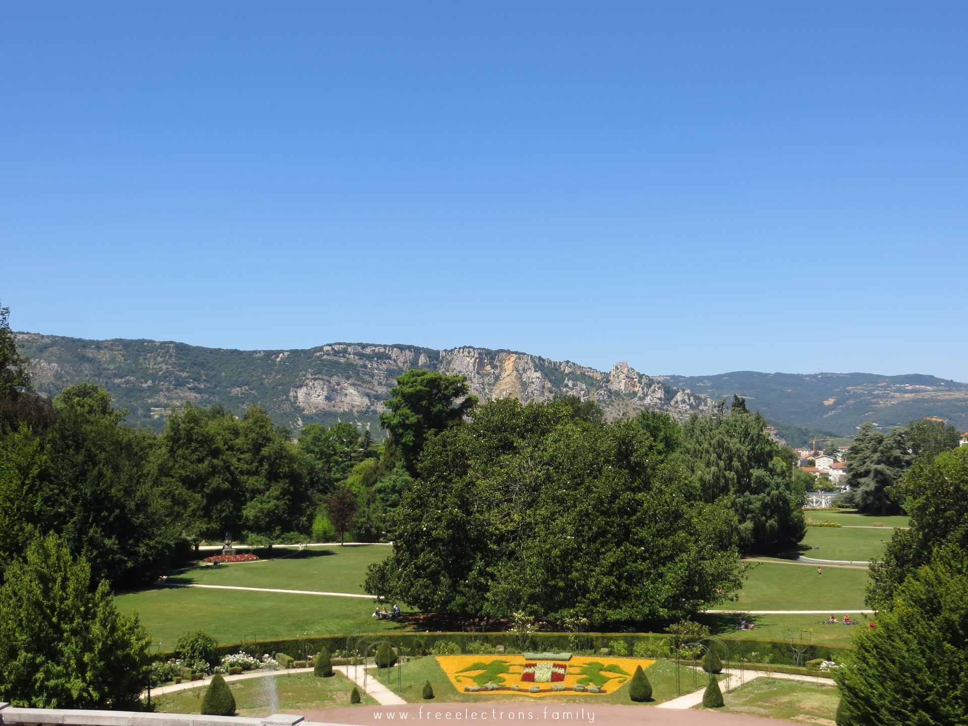 Entrance to Parc Jouvet with a view of the rocky slopes of a nearby mountain, under clear blue summer sky.  #FreeElectrons.Family - camping road trip Europe, Valence.