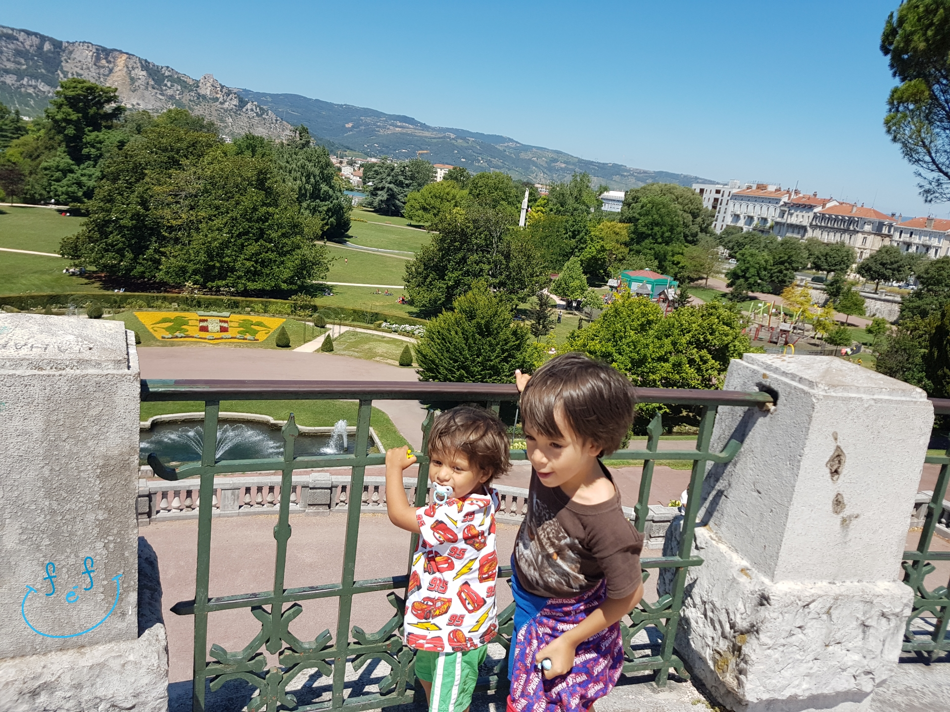 Two young children at the entrance of Parc Jouvet, overlooking the luscious greenspace of the park.  #FreeElectrons.Family - camping road trip Europe, Valence.