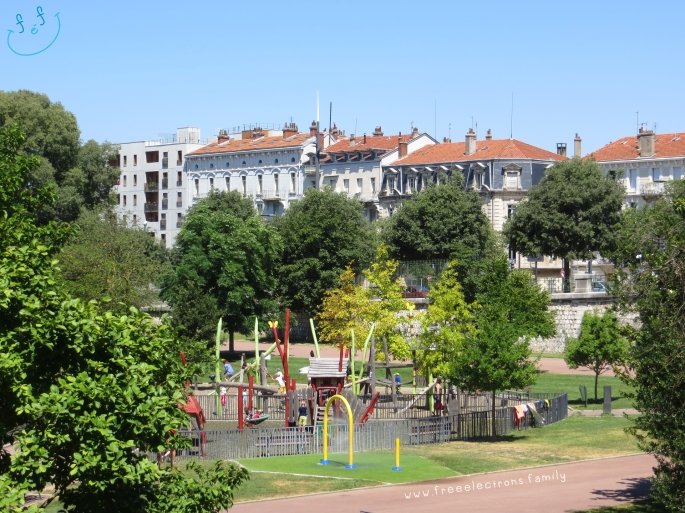 One of the playgrounds at Parc Jouvet, surrounded by trees, with the city's buildings in the background.  #FreeElectrons.Family - camping road trip Europe, Valence.