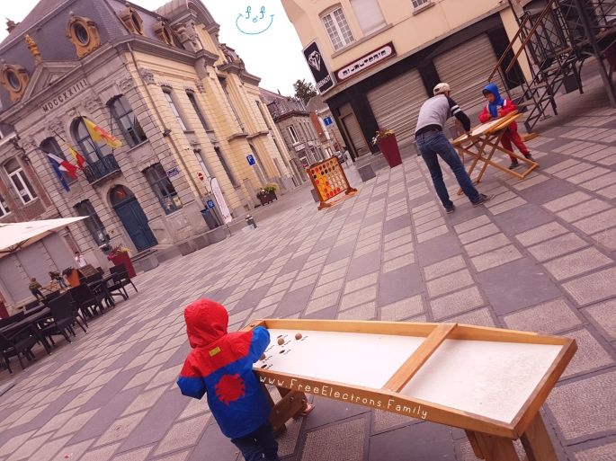 Other old-school games at Chimay town square.  Two boys in raincoats; one plays with an adult.  www.FreeElectrons.Family - camping road trip Europe 2.
