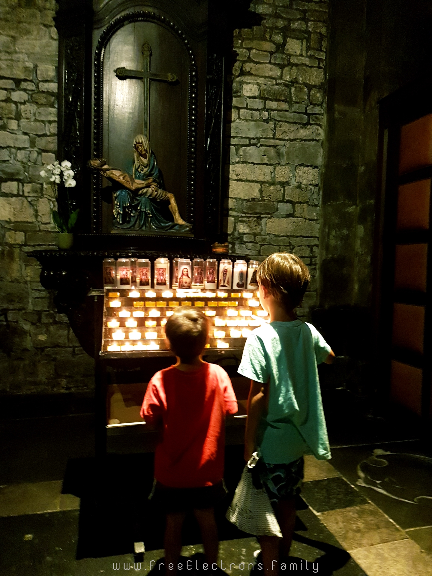 Two young children lighting candles at a chapel in the Basilica of Our Lady.  The altarpiece had an image of Mary carrying the dead body of Jesus.  #FreeElectrons.Family - camping road trip Europe Maastricht