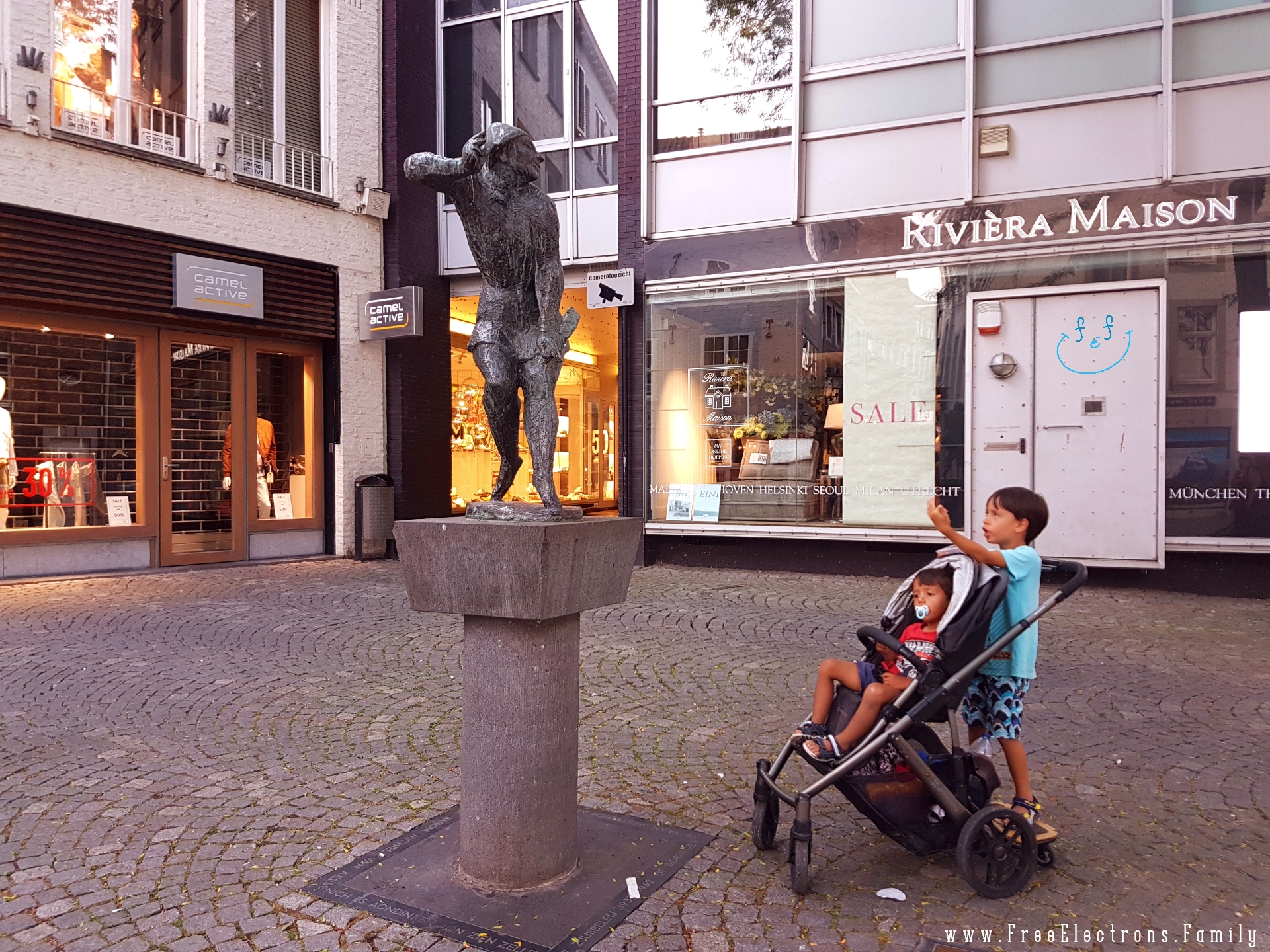 A younger child in a stroller cares less while an older one behind him mocks the statue of De Mestreechter Geis (The Spirit of Maastricht).  #FreeElectrons.Family - camping road trip Europe Maastricht