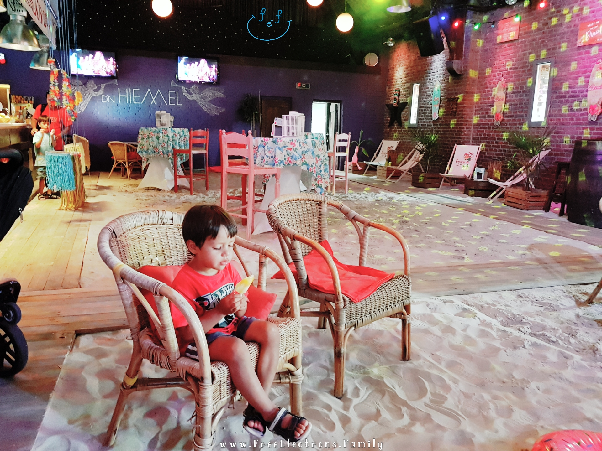 """A young child is enjoying his ice cream in a beach-themed deck/patio bar called """"D'n Hiemel"""".  #FreeElectrons.Family - camping road trip Europe Maastricht"""