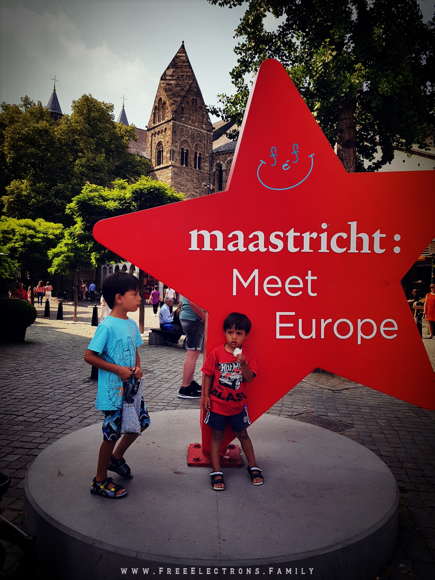 """Two young kids, looking tired, at a sign that reads """"maastricht: Meet Europe.  #FreeElectrons.Family - camping road trip Europe Maastricht"""