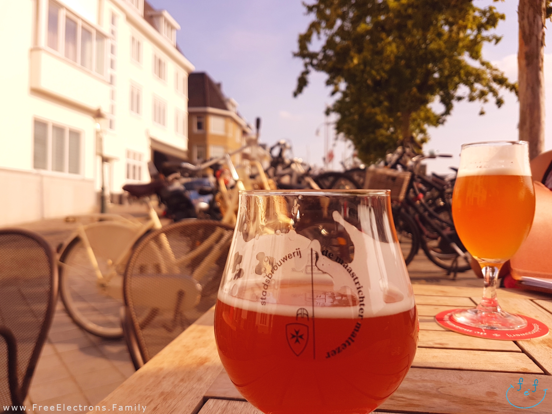 2 different beers in glasses--one blonde, the other, golden... blurred bicycles in the background.   Stadsbrouwerij: de Maastrichter Maltezer outdoor restaurant pub with its own brewery.  #FreeElectrons.Family - camping road trip Europe Maastricht