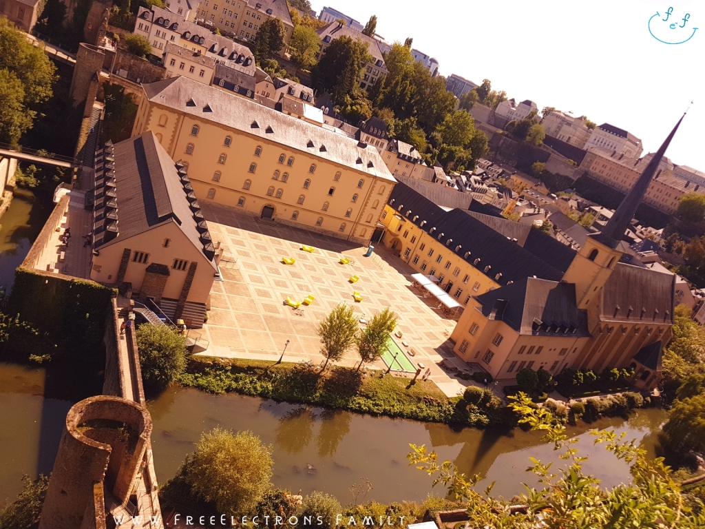 View from the rocky Casemates du Bock overlooking a valley with a courtyard of an abbey, the Alzette river and an old bridge.  Text on picture reads: www.FreeElectrons.Family with an inserted smiley face (custom icon) at a top corner.