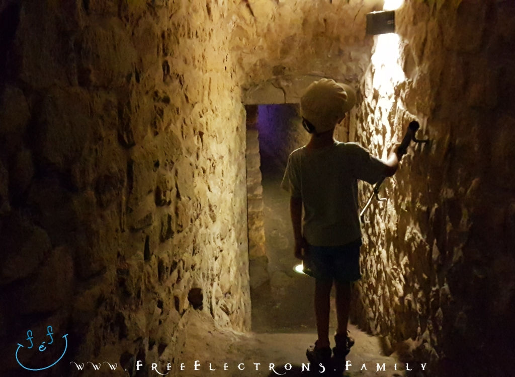 A young boy, back-turned, explores a lighted tunnel into the depths of the underground galleries of Casemates du Bock.  Text on picture reads: www.FreeElectrons.Family with an inserted smiley face (custom icon) at a bottom corner.